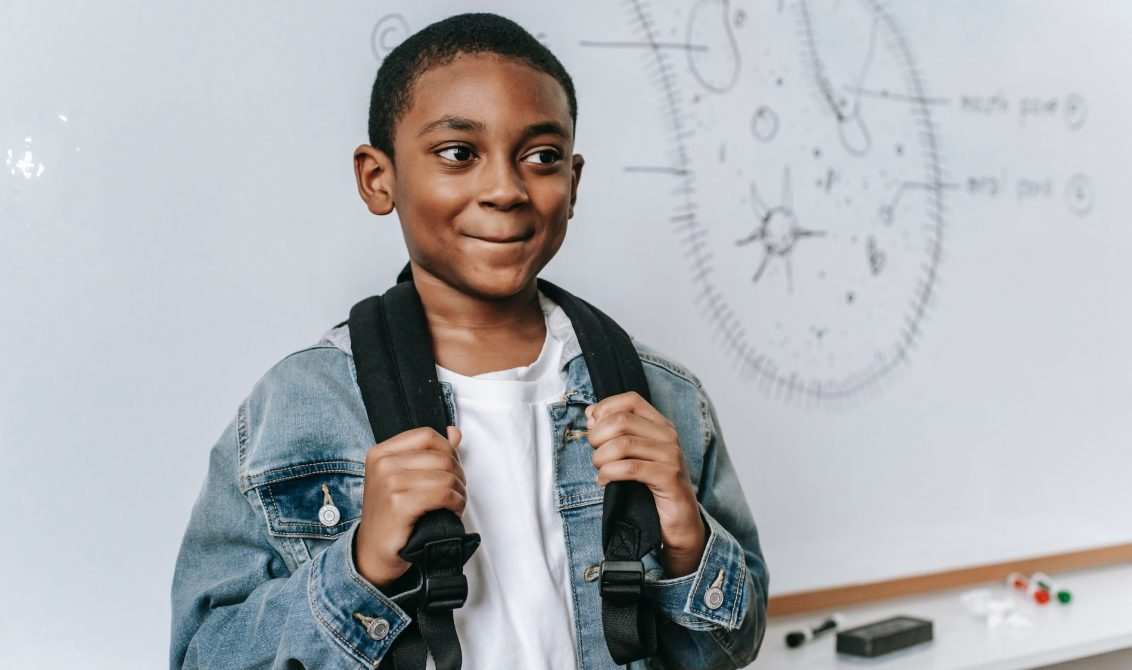 Young black student standing in front of a white board receiving some praise in the classroom