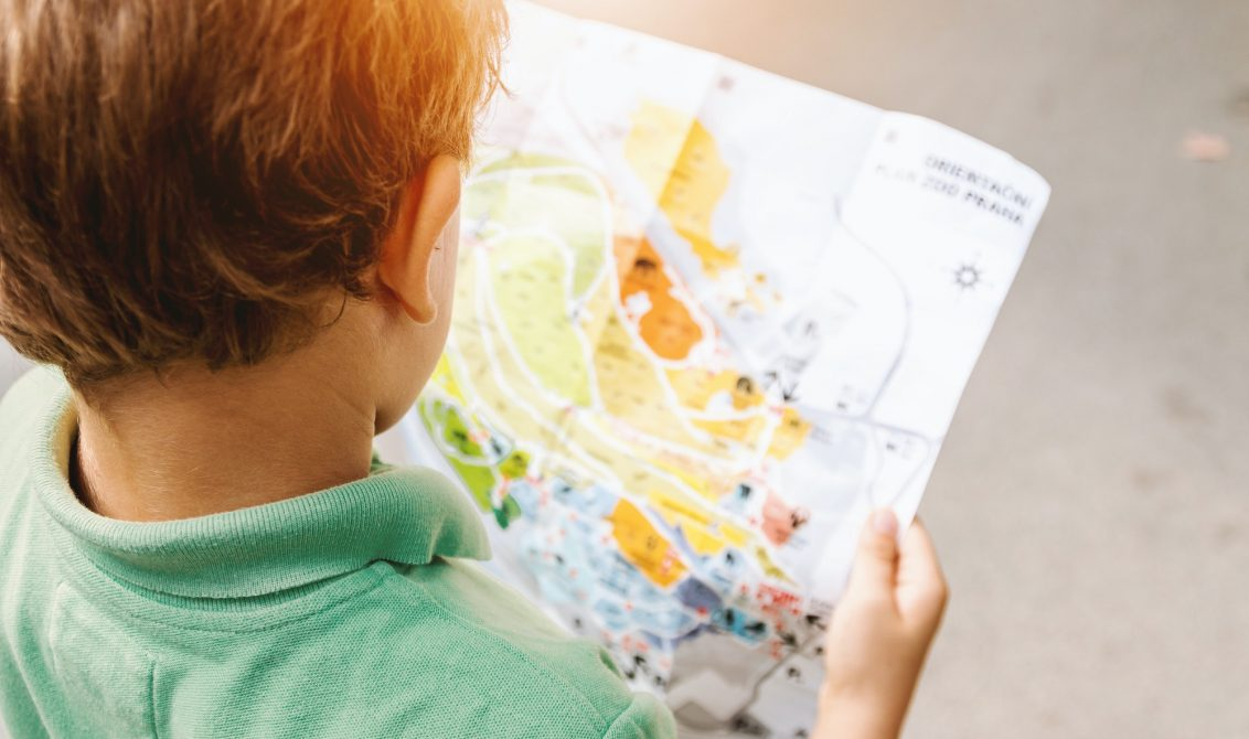 young boy reading map outside to promote offline activites